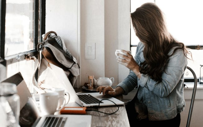 Girl sitting at desk while drinking coffee and writing