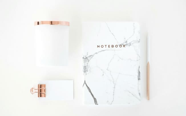 Marble notebook beside a pad of paper with a gold paper clip