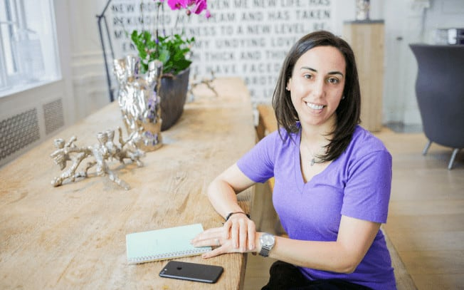 Brunette girl in purple shirt sitting at table smiling.