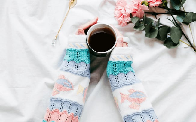 Hands holding a mug of coffee with flowers laying beside