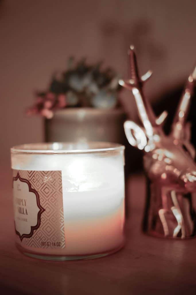 Candle on a table with an ornament beside it
