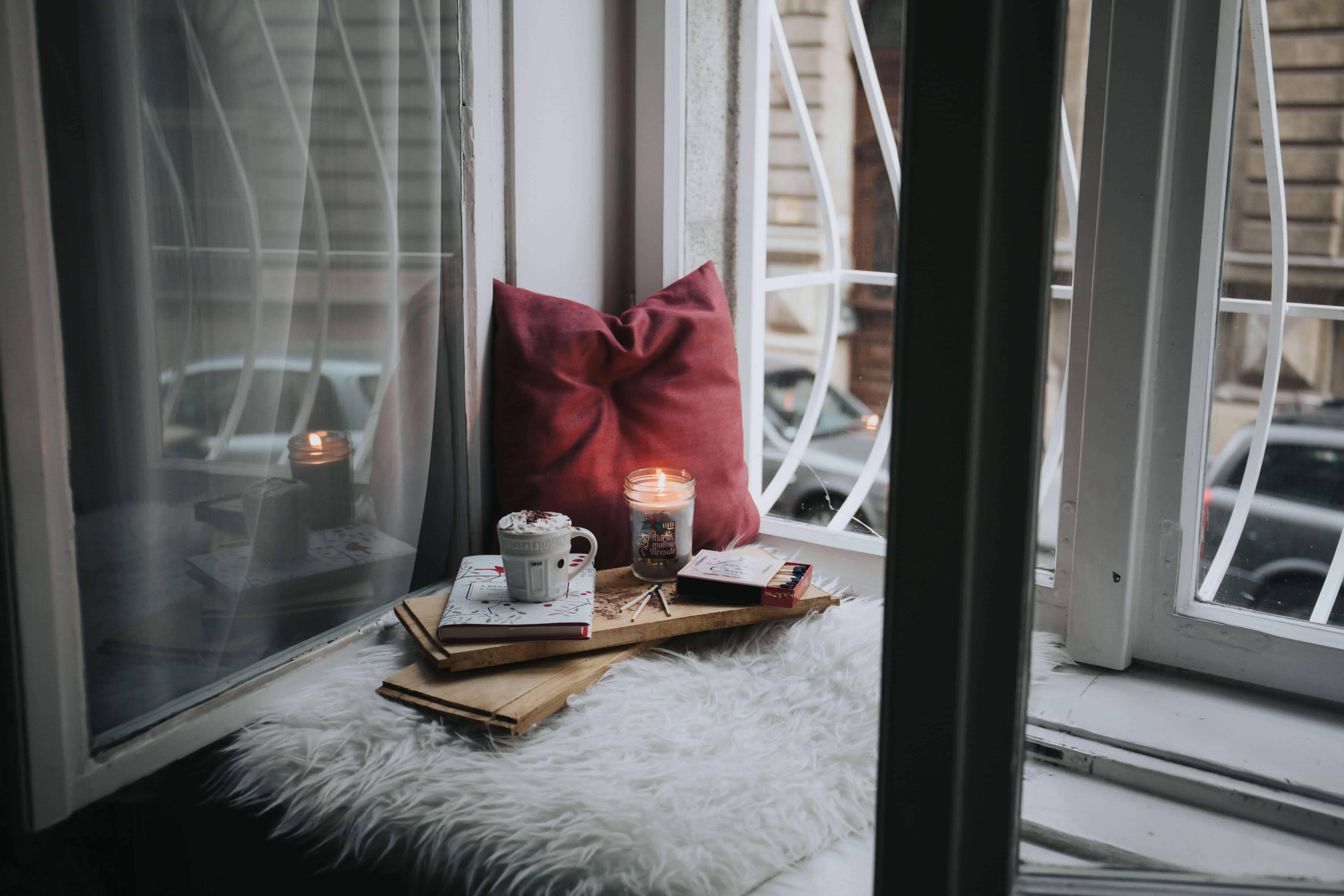 A hygge spot by the window with candles, tea and pillows.