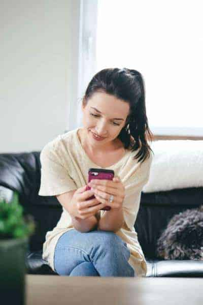 Brunette girl smiling looking at phone