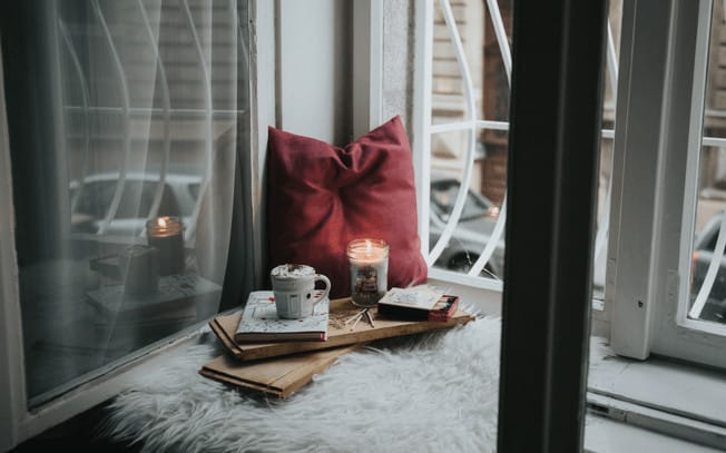 Pillow, candle and hot chocolate on top of a fuzzy blanket looking out a window