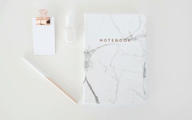 Styled photo of pencil, notebook, notepad and nailpolish