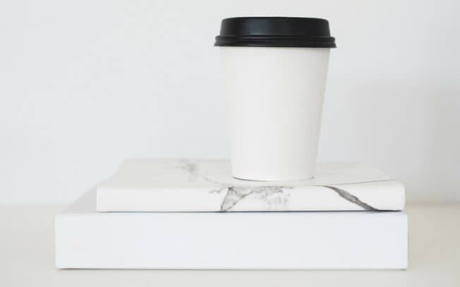 White coffee cup on two books
