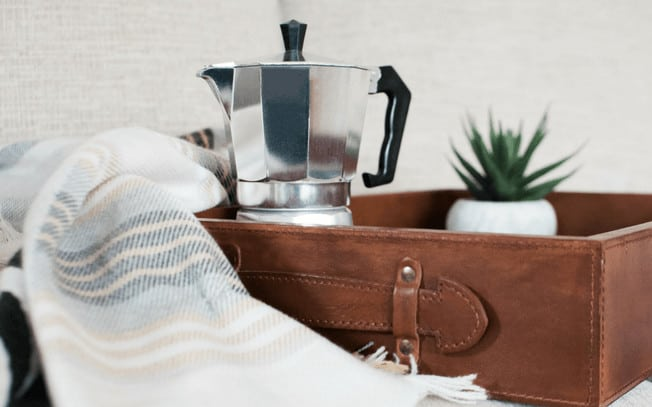 A silver coffee maker in a brown box, beside a blanket