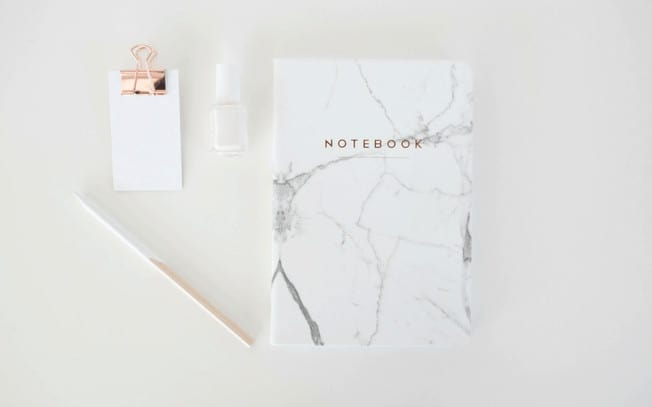 Styled photo of notebook, pencil, nailpolish and notepad
