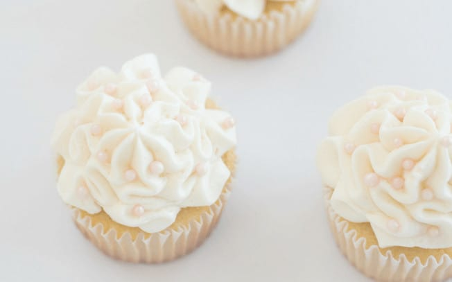 2 cupcakes with white icing on a white table