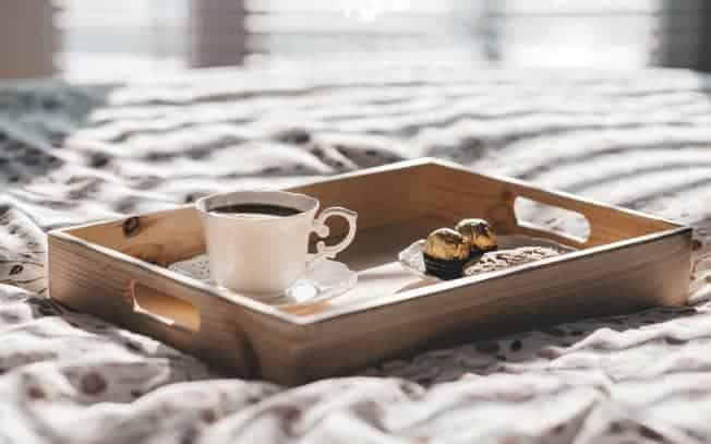 Tea and chocolates on a breakfast tray on a bed