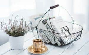 Books in a basket with a cup of tea and flowers