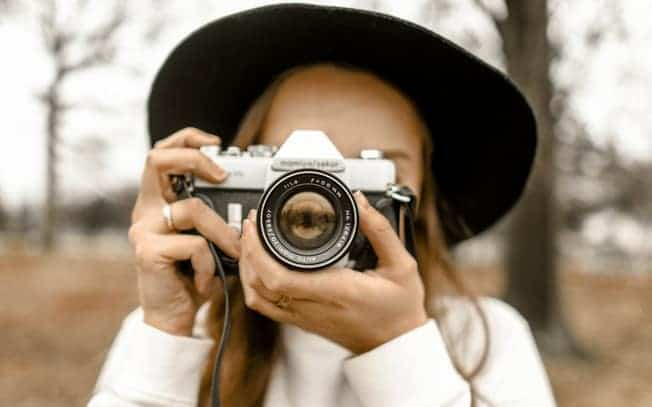 girl wearing hat and taking picture with her camera