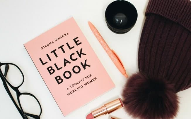 A flatlay of a book, lipstick, toque, pen and glasses