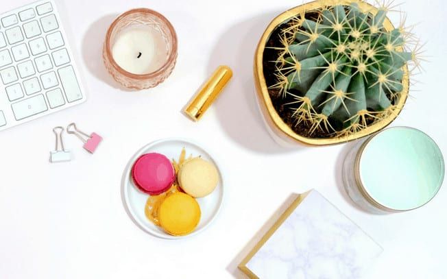 Stylized photo of macrons, cactus, candles and keyboard