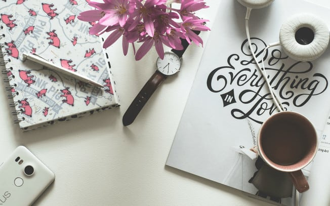 Stylized photo of watch, headphones, coffee, notepad, pen and flowers