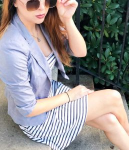 Girl sitting with striped dress wearing sunglasses