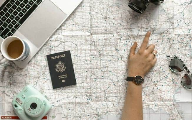 hand pointing to map beside passport, laptop, coffee, sunglasses and camera
