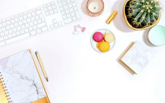 keyboard, macarons, cactus and notebook styled on a desk
