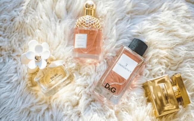 four perfumes laying on a white shag rug