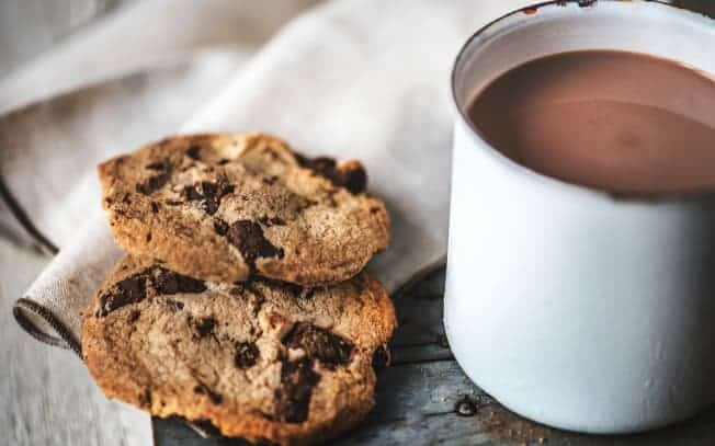 Two cookies beside a mug of hot chocolate