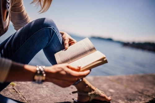 A girl reading a book by the water