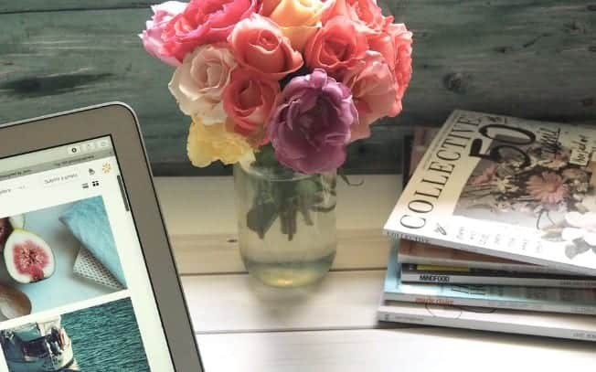 Flowers beside a stack of magazines and a laptop
