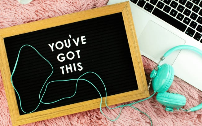 """A sign that says """"you've got this"""" with teal headphones and laptop styled on a pink carpet"""