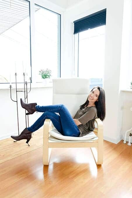 Brunette woman sitting in a chair smiling at the camera