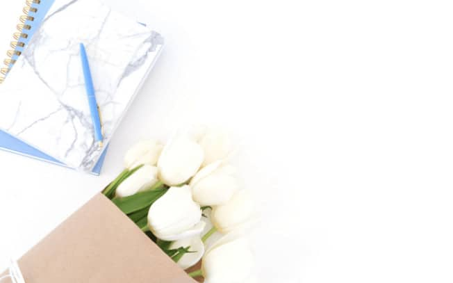 White flowers beside marble notebook