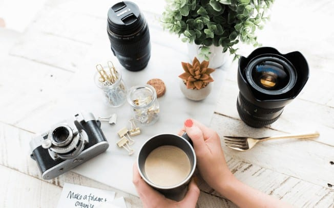 birds-eye view of hands holding a cup of coffee with camera lenses and a plant.