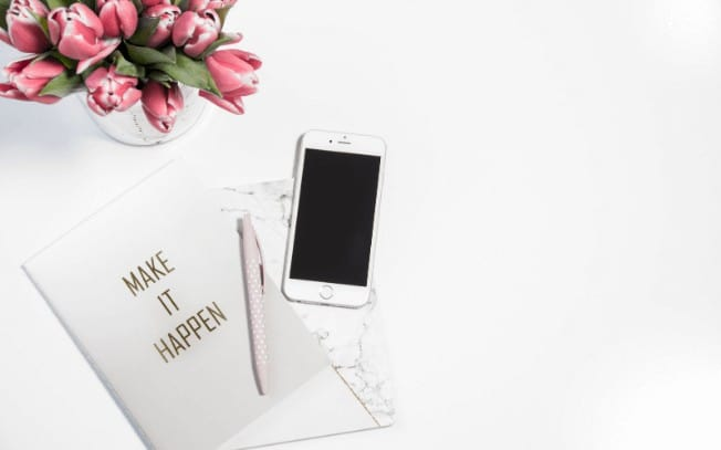 an iphone beside flowers and a pen with paper
