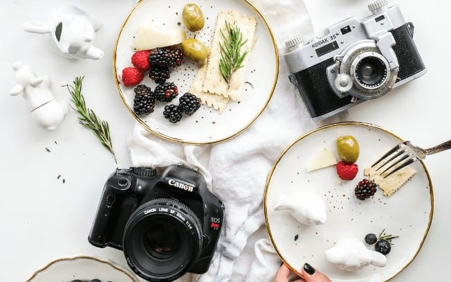 two cameras beside a plate of crackers, cheese, olives and fruit