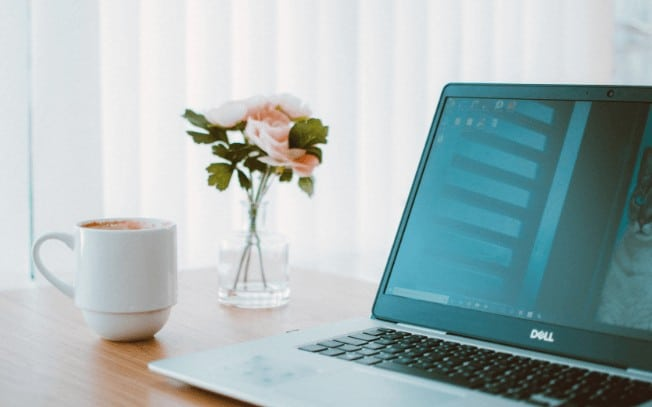 Pink flowers beside a laptop and cup of coffee on a desk