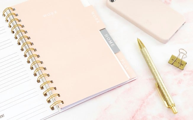 notepad and gold pen on pink marble table