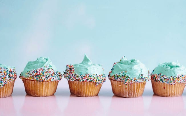 Cupcakes with blue icing on a pink table