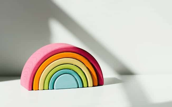 A rainbow toy on a white desk