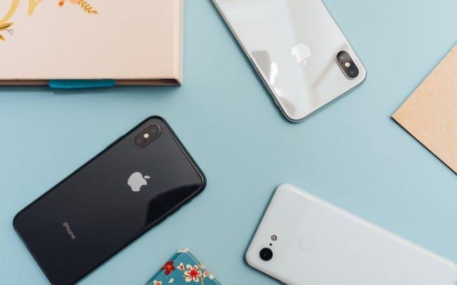 3 iPhones on a blue desk
