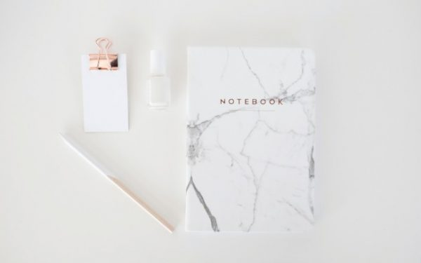 Notebook, pen, paper and nail polish on a white desk