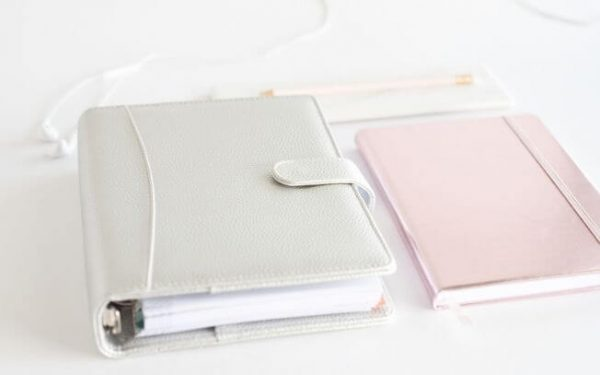A grey notebook and a pink notebook on a table