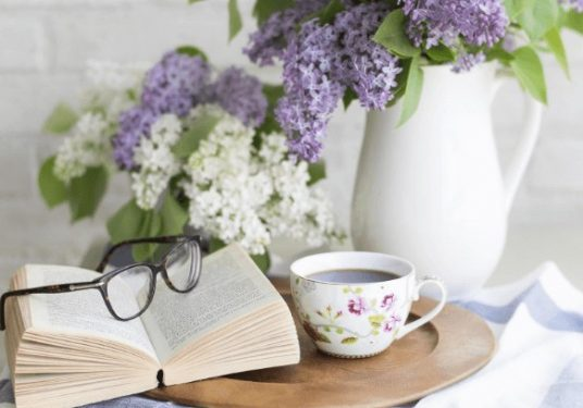 A book on a table with white and purple flowers, beside a cup of tea and glasses laying on top of the book.