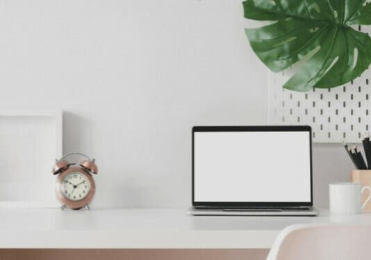 Laptop siting on a desk beside a plant and a clock.