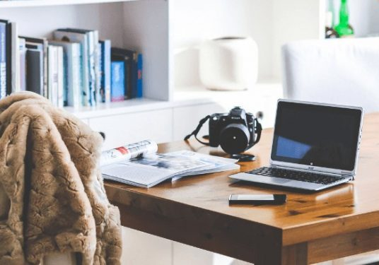 A home office with a laptop, camera and magazine on a wood table