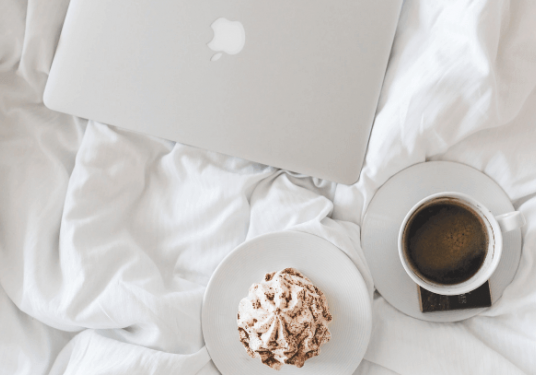 Laptop, coffee and pastry styled on a bed