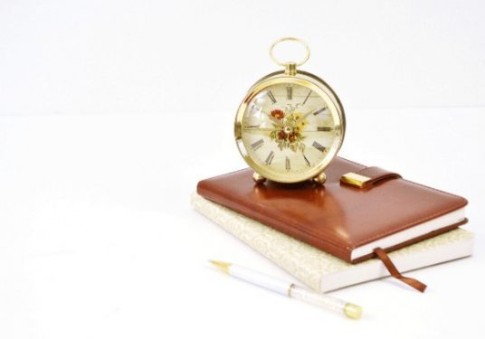 A clock sitting on top of two books