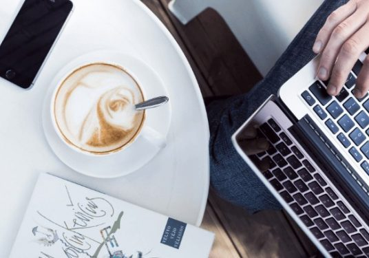Latte and laptop on a white desk