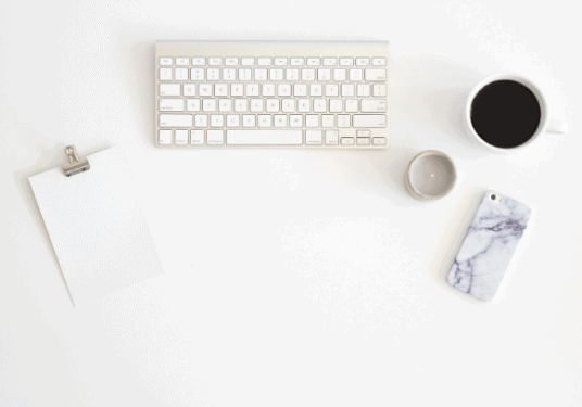 A styled stock photo of a keyboard, a cup of coffee, a notepad and a cell phone all on a desk.