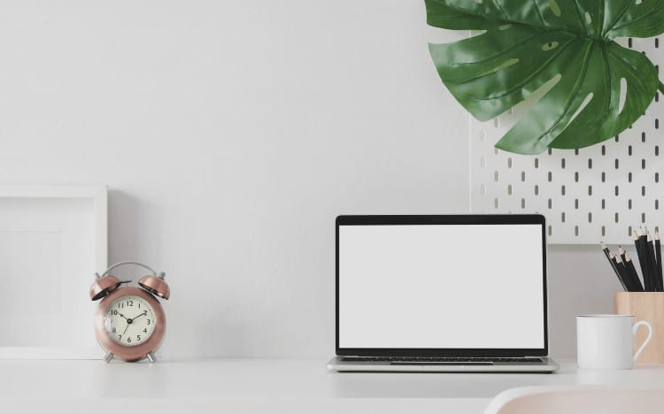 A styled photo of a desk with a clock, a laptop and a leaf