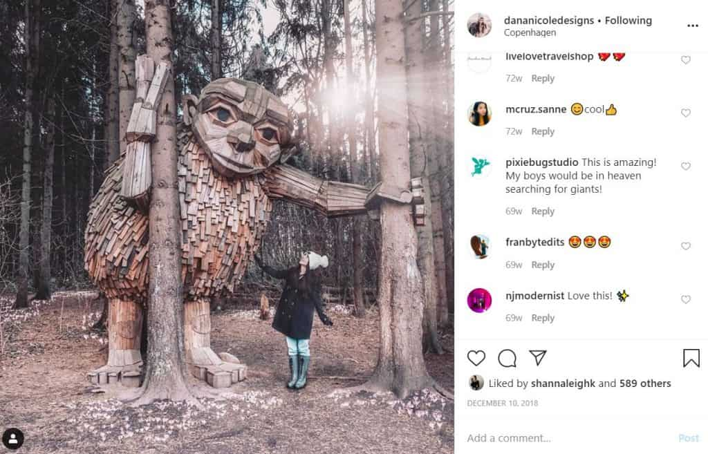Screenshot of an Instagram feed image where a girl is looking up at a giant wooden statue of a giant in the woods