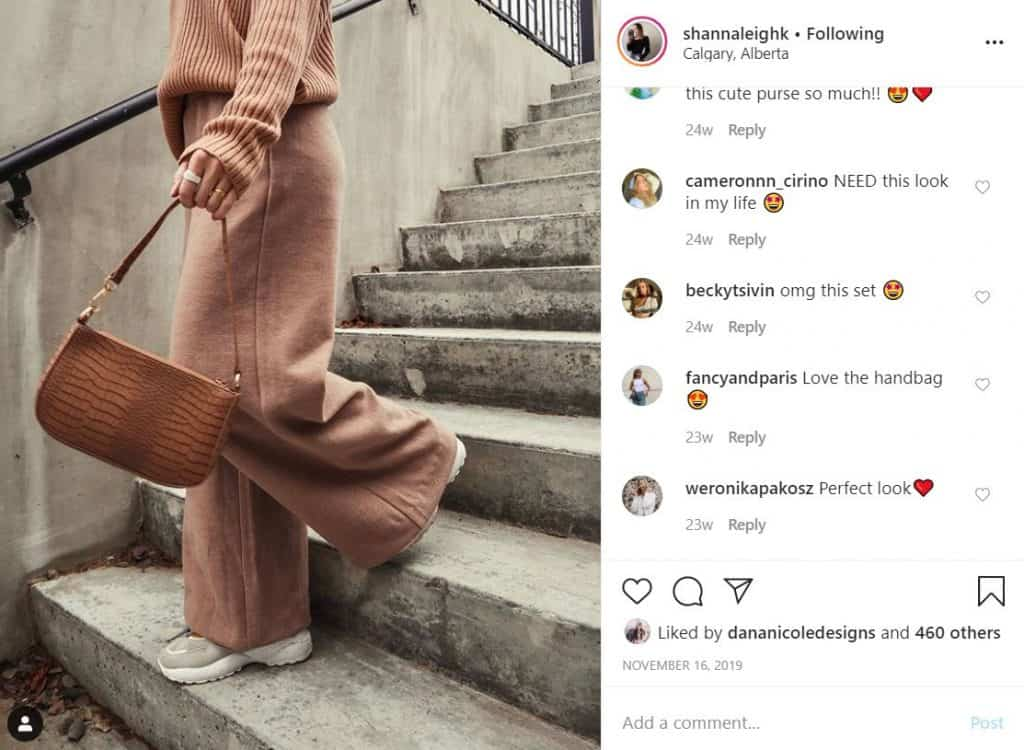 Screenshot of an Instagram image of a girl walking down the stairs holding a purse. The image is taken from the neck down.
